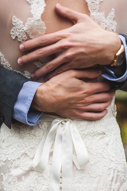 Groom's hands embracing bride