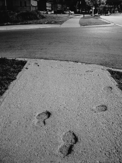footprints in sidewalk at night on bristol rd. Mississauga