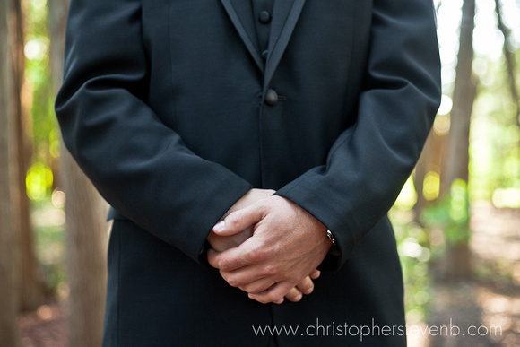 Groom's hands folded while waiting for bride during first look.