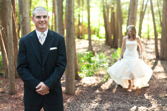 groom smiling with bride approaching in forest