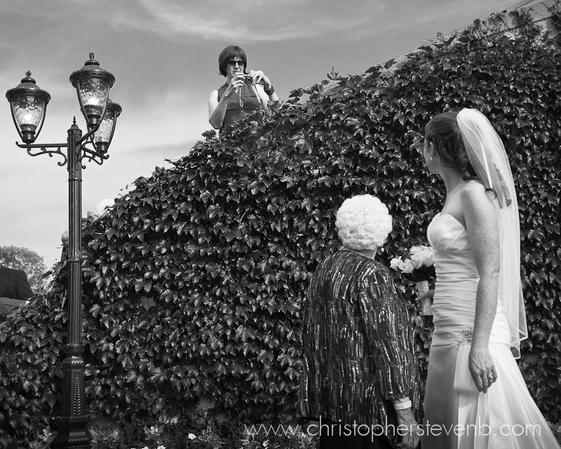 funny wedding photo with guest photographing bride