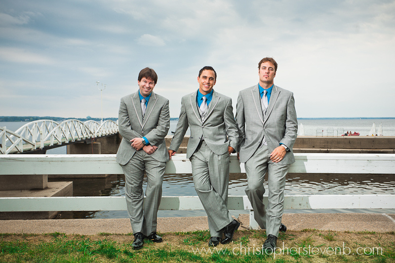 formal portrait of groom and his groomsmen in front of moody sky at the Britannia Yacht Club