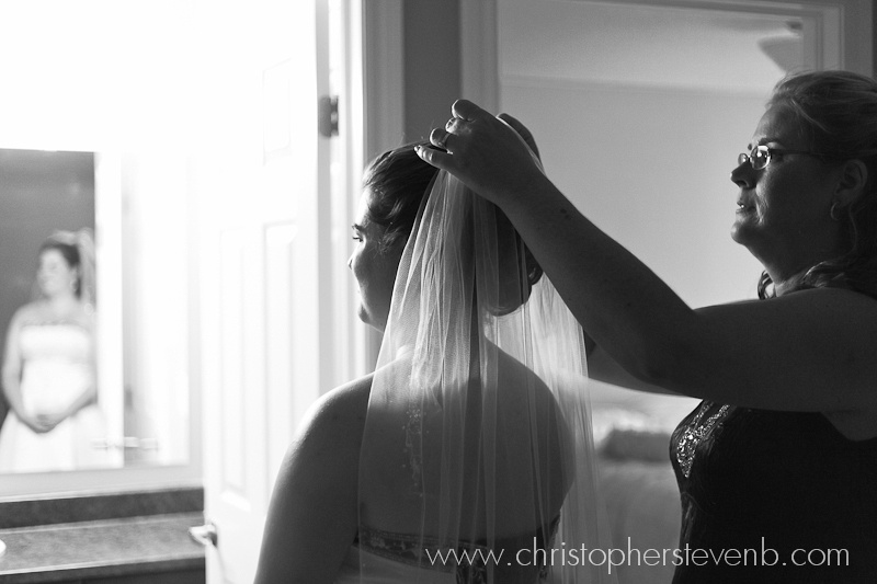bride getting ready with mother adjusting her veil