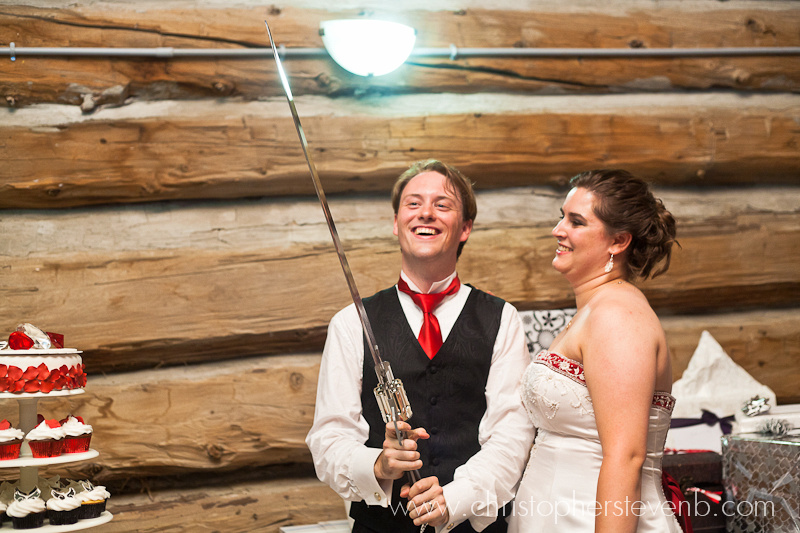 groom smiling and holding special cake cutting knife