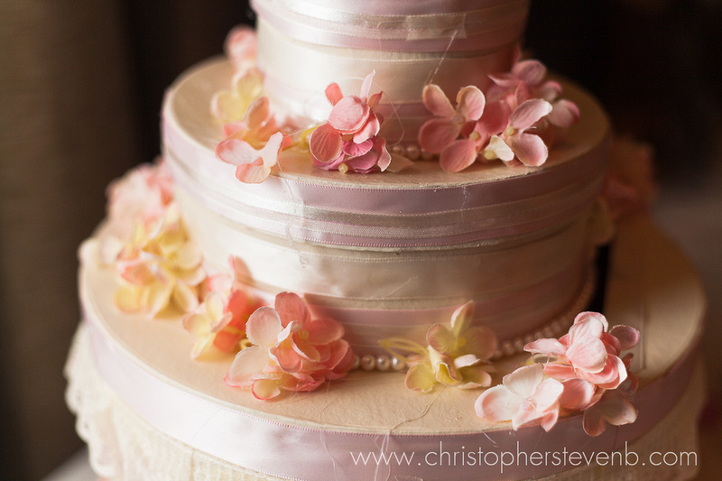pink country chic wedding cake with pearls, flowers and ribbons