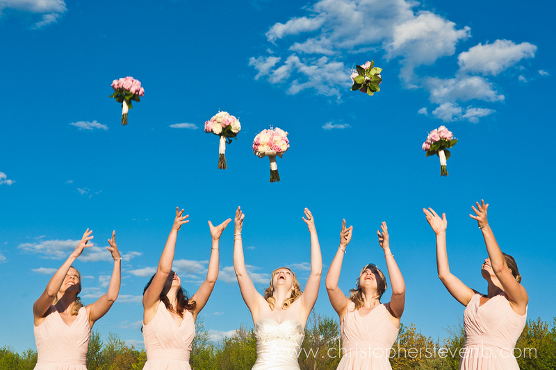 bridesmaids tossing their bouquets in the air in front of blue sky