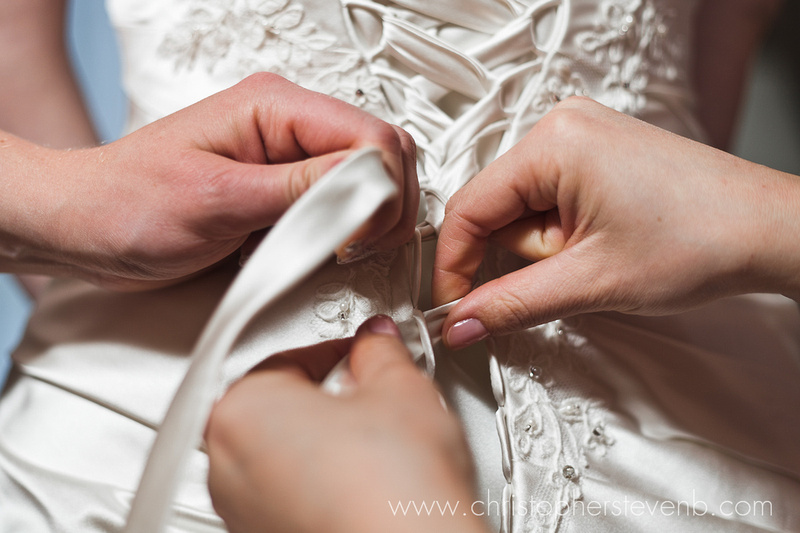 Ribbon of dress being tied by bridesmaids
