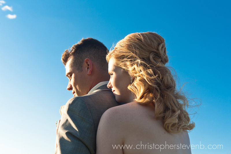 bride and groom romantic photo with blue sky looking into the sun