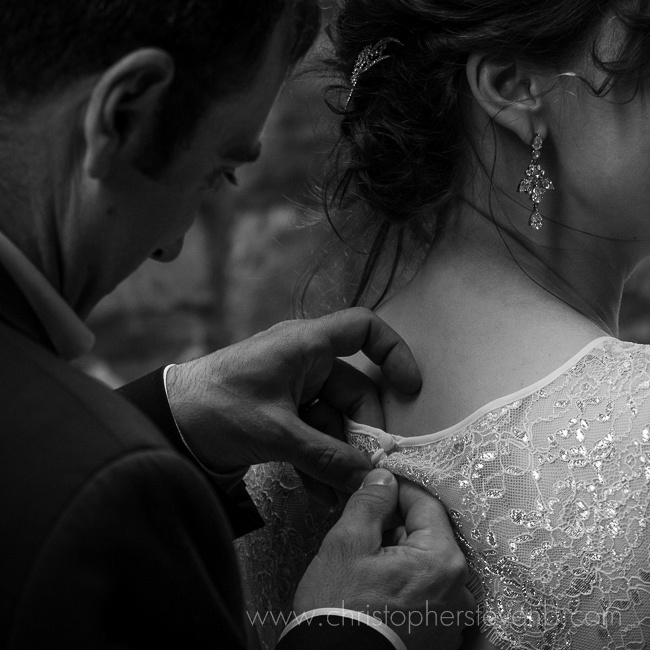 romantic photo of groom fastening button on bride's dress
