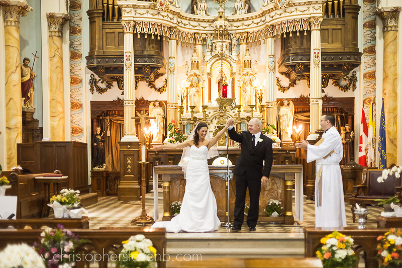 bride and groom excited, raising arms at front of Holy Trinity catholic church