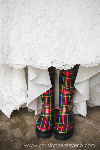 bride wearing rubber boots at rainy country wedding