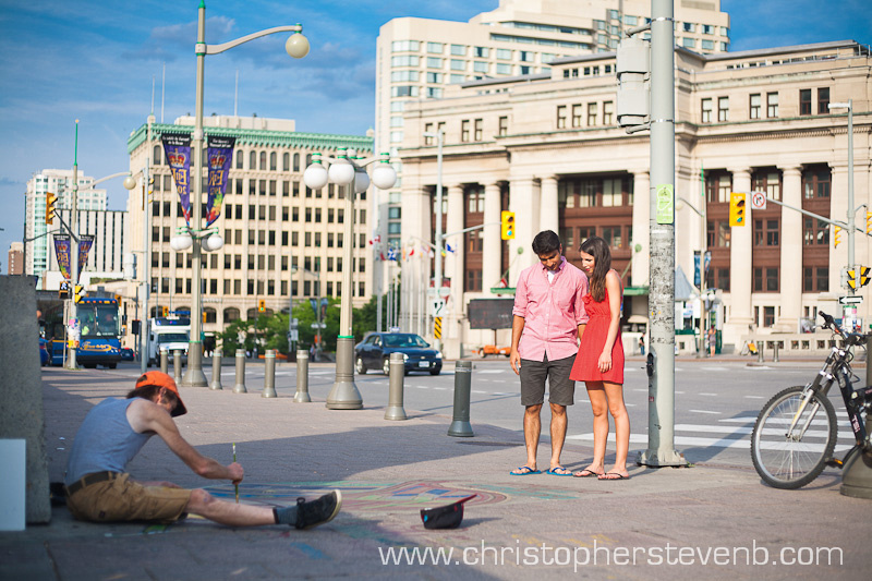 couple watching sidewalk artist work on Laurier