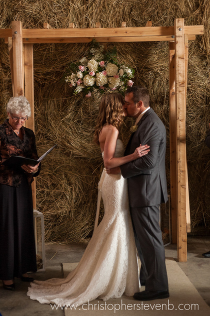 bride and groom kissing during barn wedding