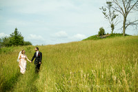 romantic photo of bride and groom in the country with long grass