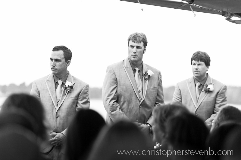 Groom and groomsmen standing seriously
