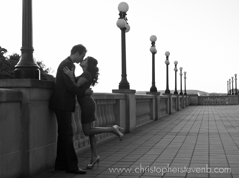 black and white photo of couple kissing on deck next to chateau laurier with lamps