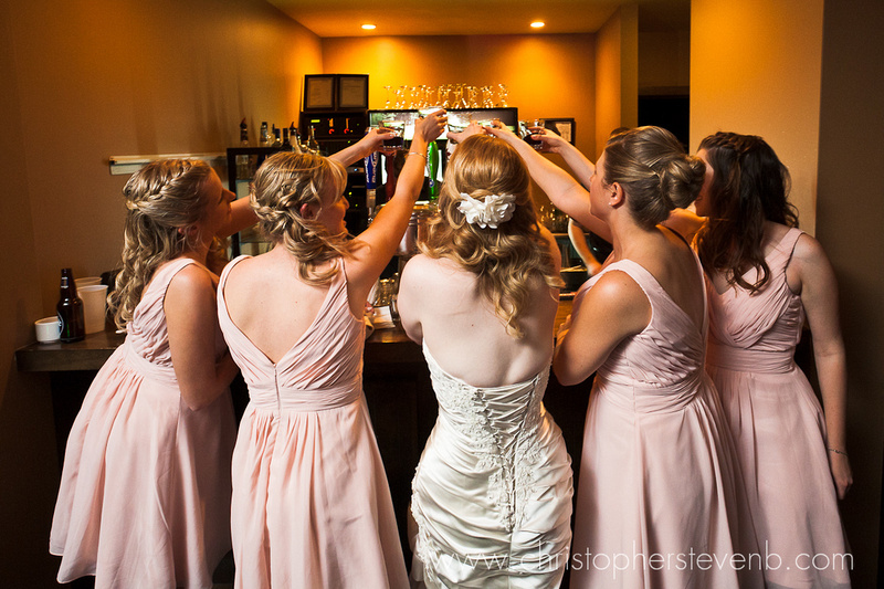 bridesmaids toast a drink at the bar during reception