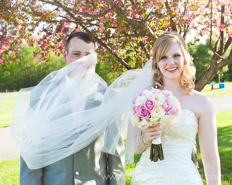 funny photo of bride's veil falling on groom