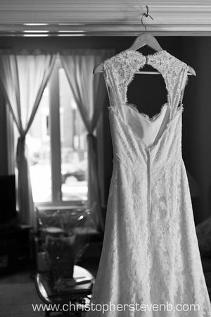 open-back wedding dress hanging in door frame in front of window