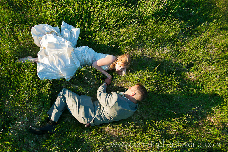 artistic photo of bride and groom laying on the grass with the sun casting long shadows