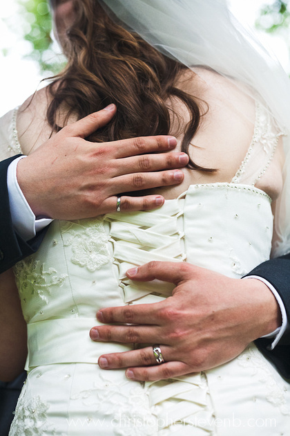 groom's hand on back showing bride's dress