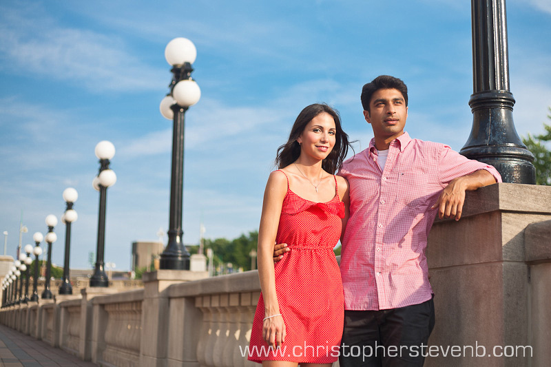 engaged couple with lamp posts and blue sky near chateau laurier