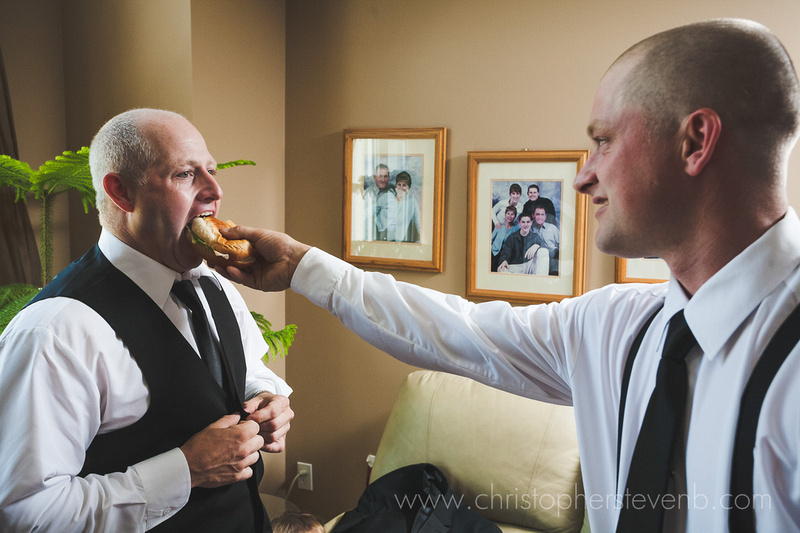 Funny and candid photo of groom taking a bite of hamburger and being fed by groomsman