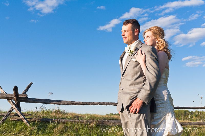 romantic photo of the wedding couple embracing under a blue sky at country wedding