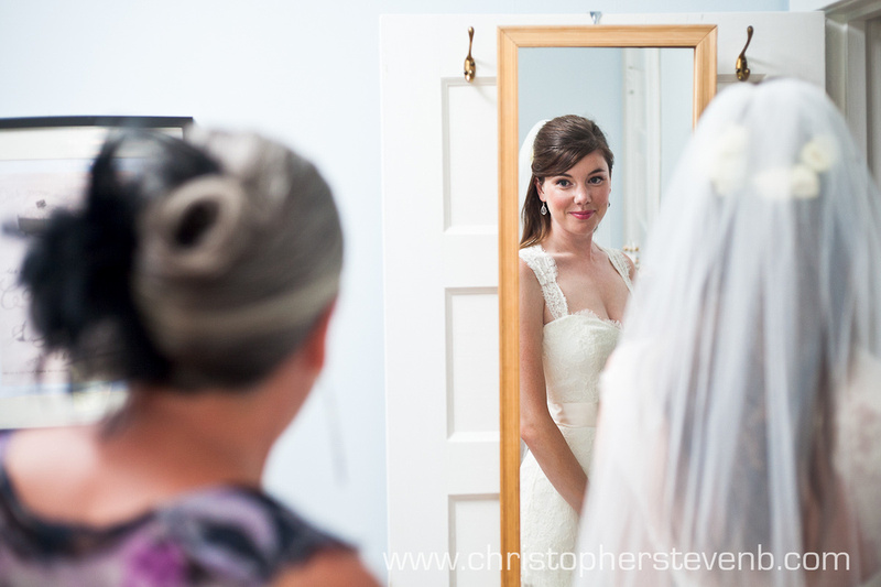 bride looks in mirror at mother as she prepares for wedding day