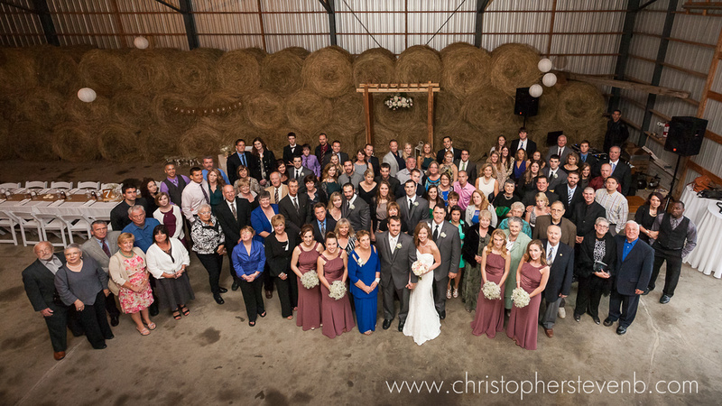 big group photo of wedding party in barn with hay bales