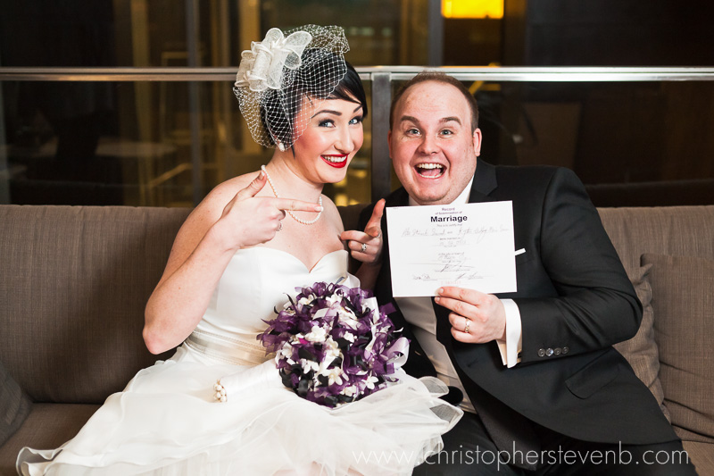 wedding couple being funny pointing at marriage certificate after wedding ceremony
