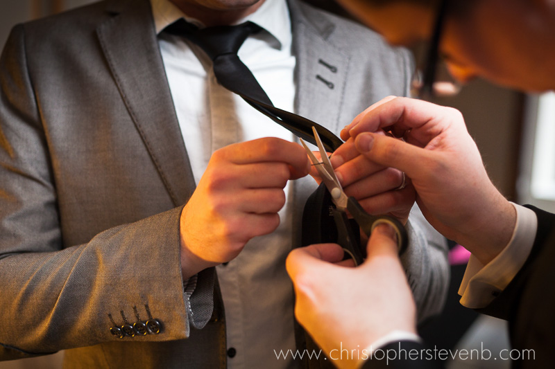 groomsmen using scissors while getting ready for stylish wedding