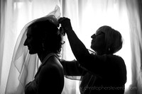 silhouette of mother of bride putting veil on