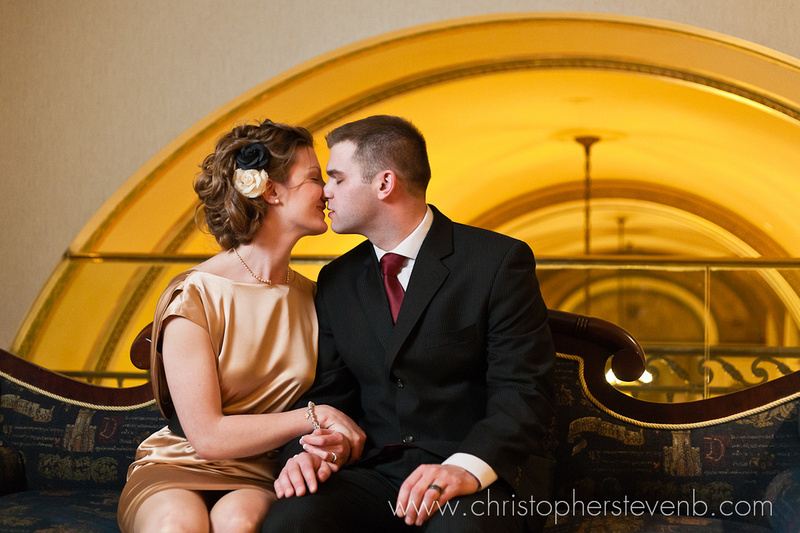 bride and groom kiss on the mezzanine level of chateau laurier