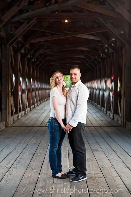 couple posing for engagement photo on bridge
