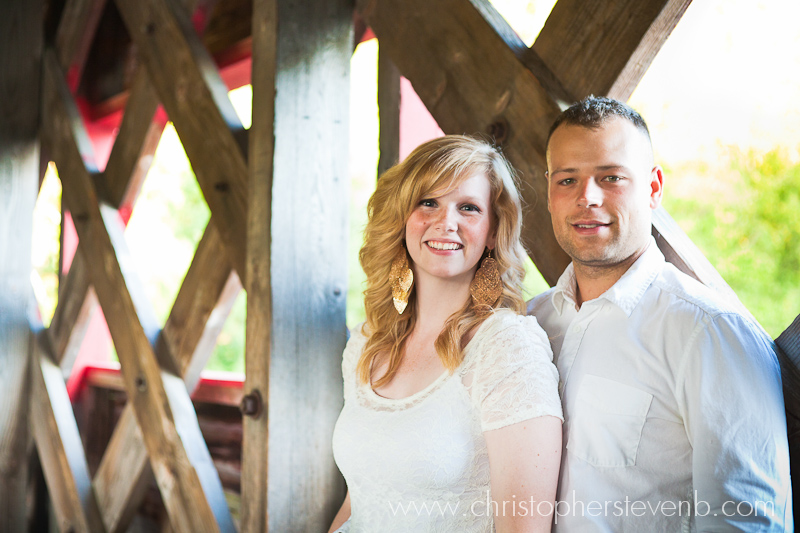 Couple in front of wooden lattices of the covered bridge