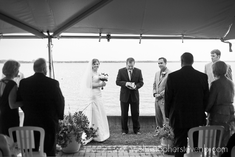Guests and wedding couple under tent during ceremony