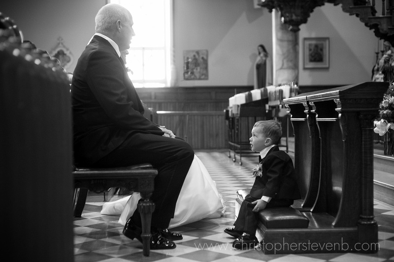funny photo of wedding couple's child sitting on kneeling bench during catholic wedding