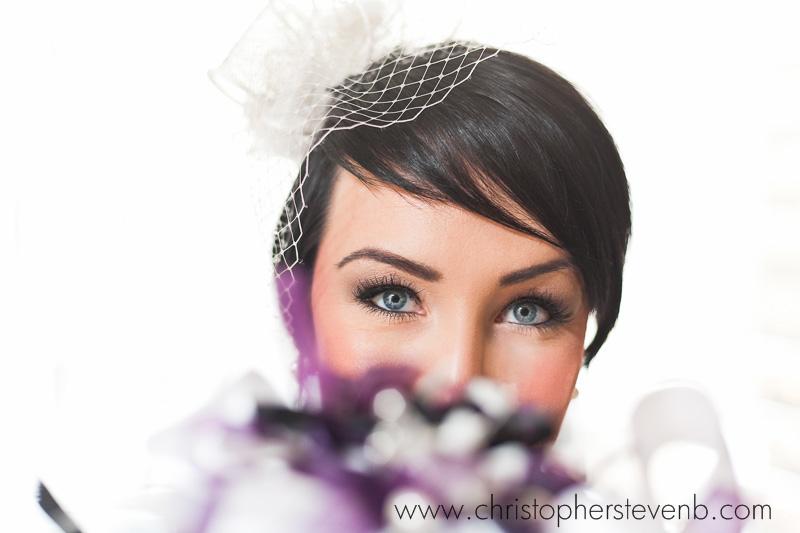 bride peeking over bouquet wearing birdcage veil