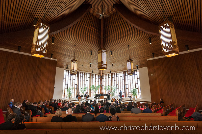 Wide view of inside of First Unitarian Congregation of Ottawa church with rich wooden beams and modern design